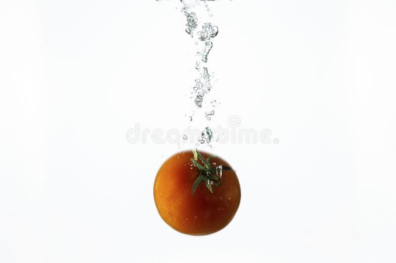 Close up view splashing water and red tomato  on white background. Beautiful backgrounds stock photos
