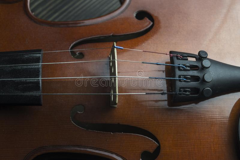 Violin lying on wooden background. Close up view of strings ofl brown violin lying on wooden background royalty free stock images