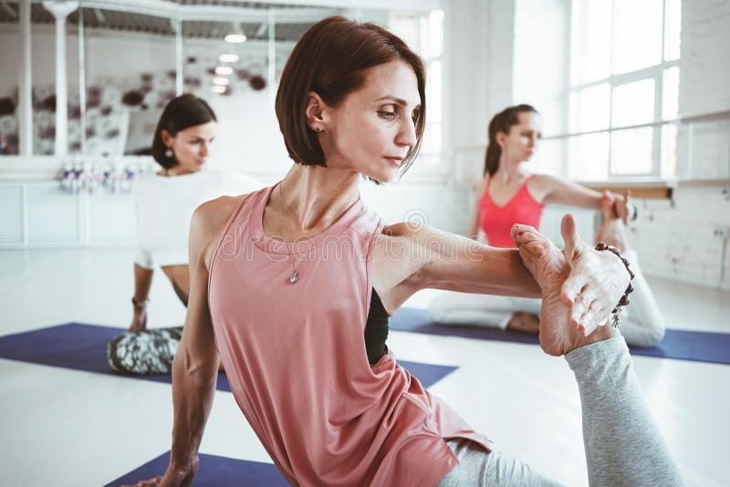 Close up view strong adult woman practicing yoga poses for maintaining health care. Group of active people doing fithess stretchin. Close up view strong adult stock images