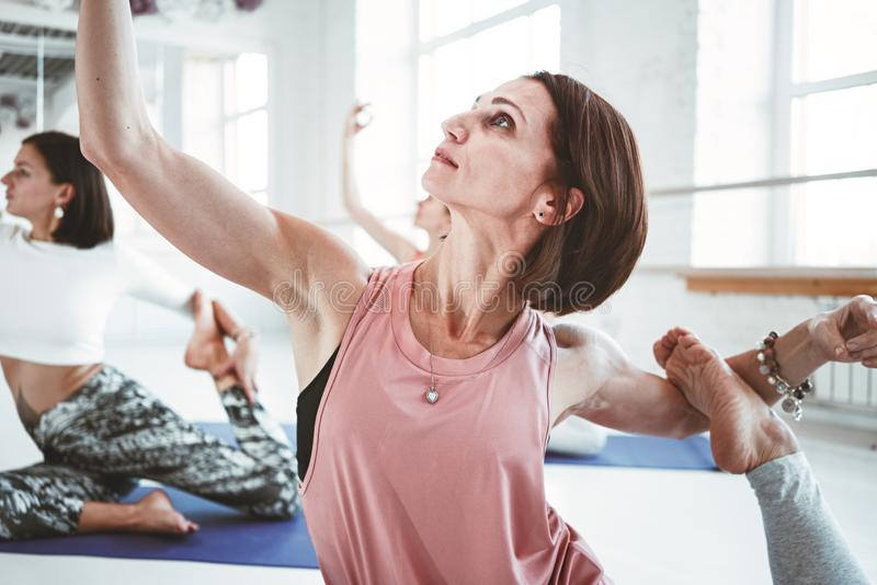 Close-up view on strong healthy woman practicing yoga exerciese on fitness mat in white sport class. Close-up view on strong healthy women practicing yoga royalty free stock image