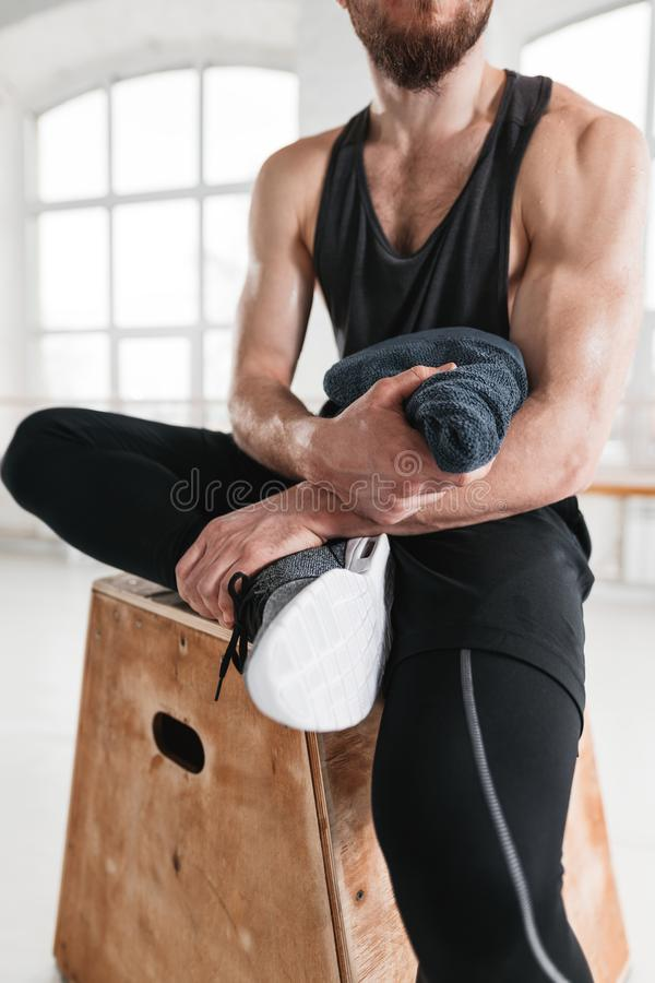Close up view on strong male athlete resting on wooden box after cross intense in workout gym stock image
