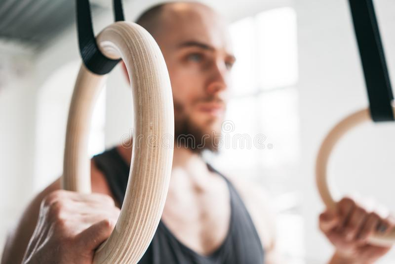 Close up view on strong man doing exercise on to gymnastic rings at gym royalty free stock image