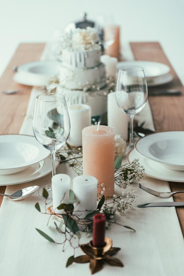 close up view of stylish table setting with candles, empty wineglasses and plates royalty free stock photography
