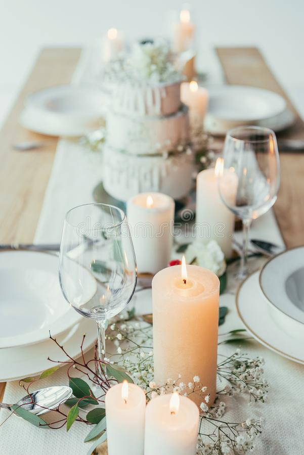 Close up view of stylish table setting with candles, empty wineglasses and plates. For rustic wedding stock photos