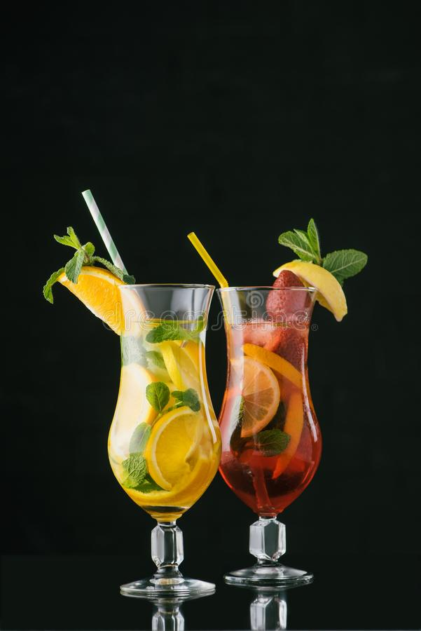 Close up view of summer fresh cocktails with mint and citrus pieces. Isolated on black royalty free stock image