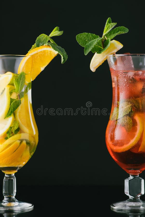 Close up view of summer fresh cocktails with mint and citrus pieces. Isolated on black stock photo