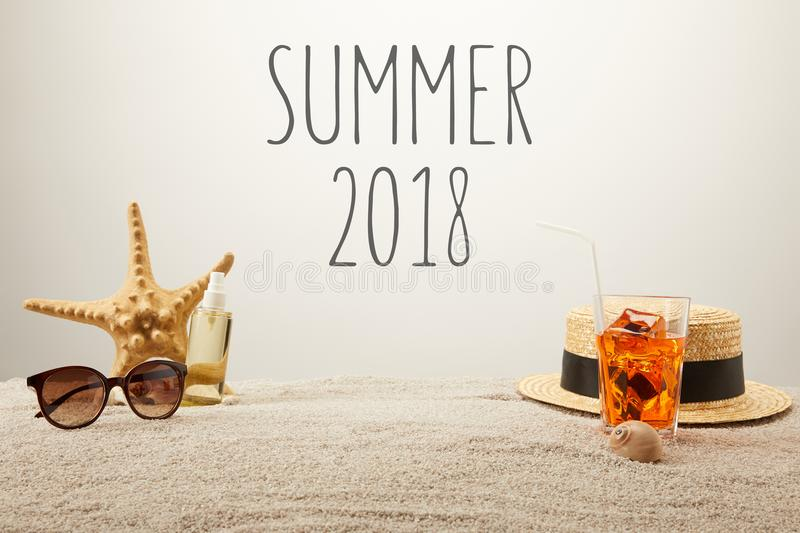Close up view of summer 2018 lettering, cocktail with ice, straw hat, sunglasses and tanning oil on sand on grey backdrop stock photo