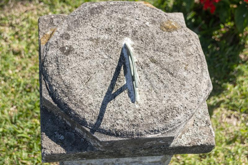 A Sun Dial. A close up view of a sun dial on a concrete stand in an outside garden royalty free stock photo