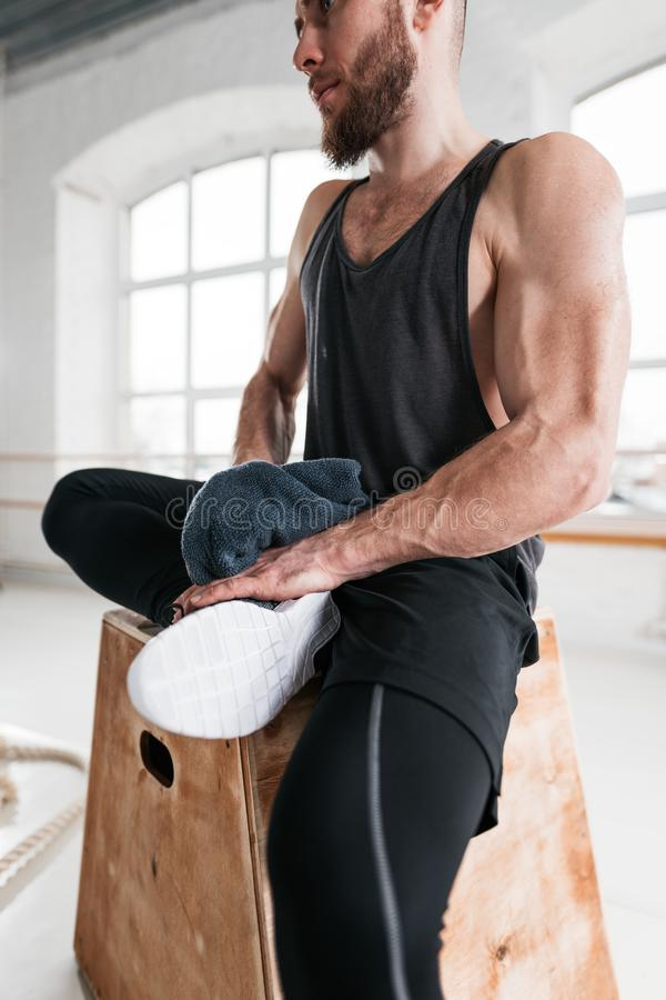 Professional workout sportsman sitting on box in sport hall stock photo