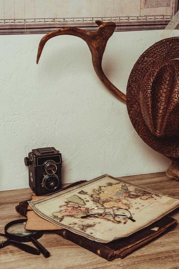 Close up view of table with map, eyeglasses, magnifying glasses, retro photo camera. And decorative horns stock photo