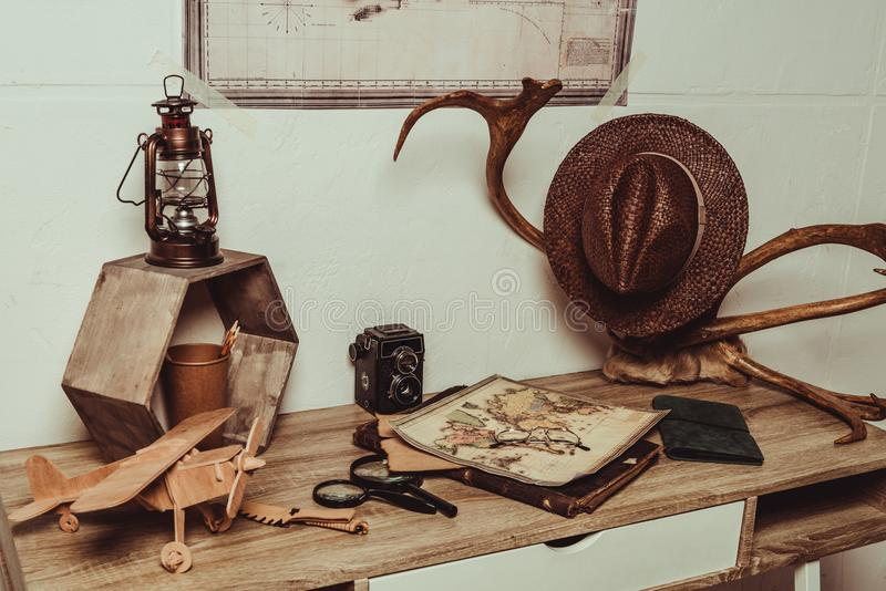 Close up view of table with map, eyeglasses, magnifying glasses, retro photo camera. And decorative horns stock photos