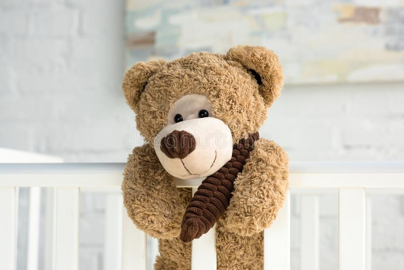 Close up view of teddy bear hanging on white wooden baby crib. In room stock images