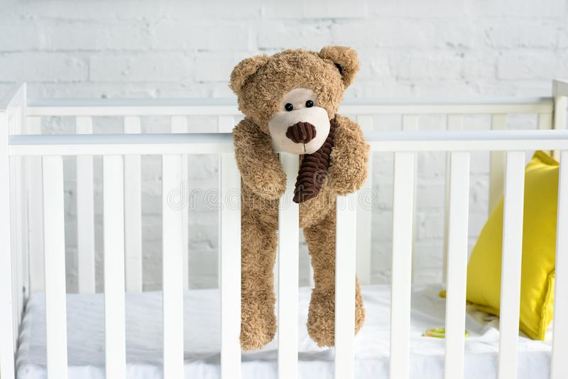 Close up view of teddy bear hanging on white wooden baby crib. In room royalty free stock image
