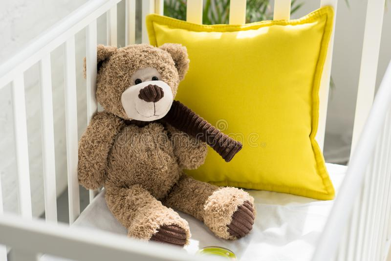 Close up view of teddy bear and yellow pillow in baby crib. At home stock photos