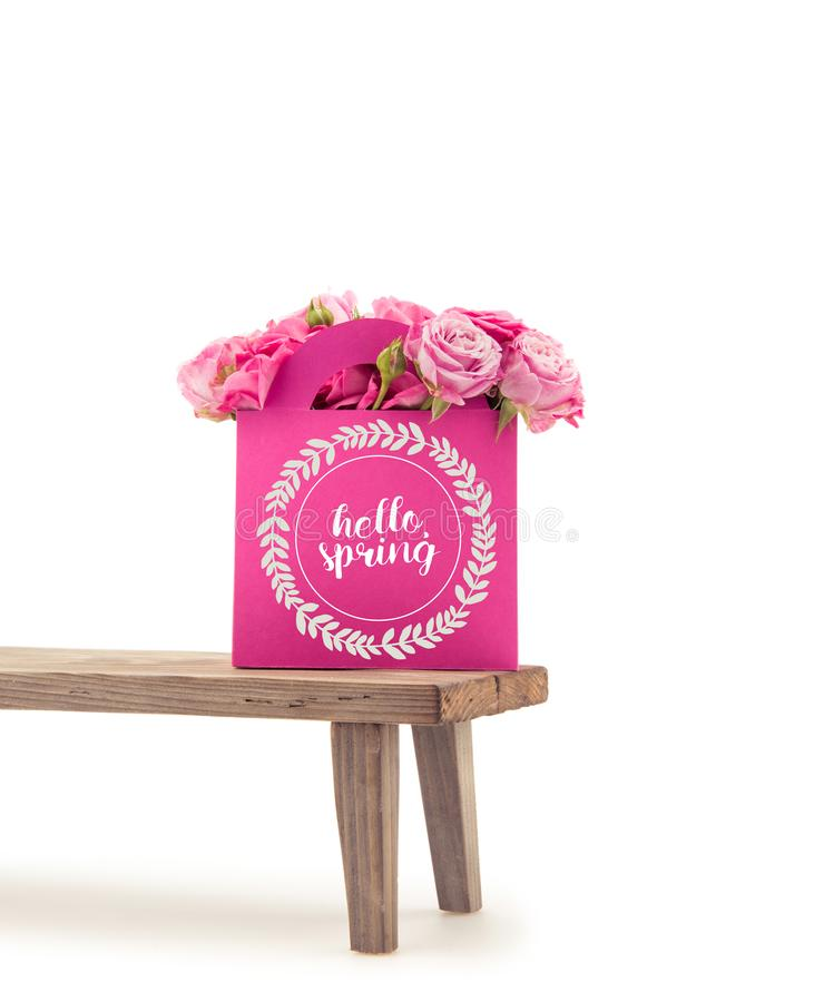 Close-up view of tender blooming rose flowers in pink paper bag with HELLO SPRING lettering on wooden bench. Isolated on white stock illustration