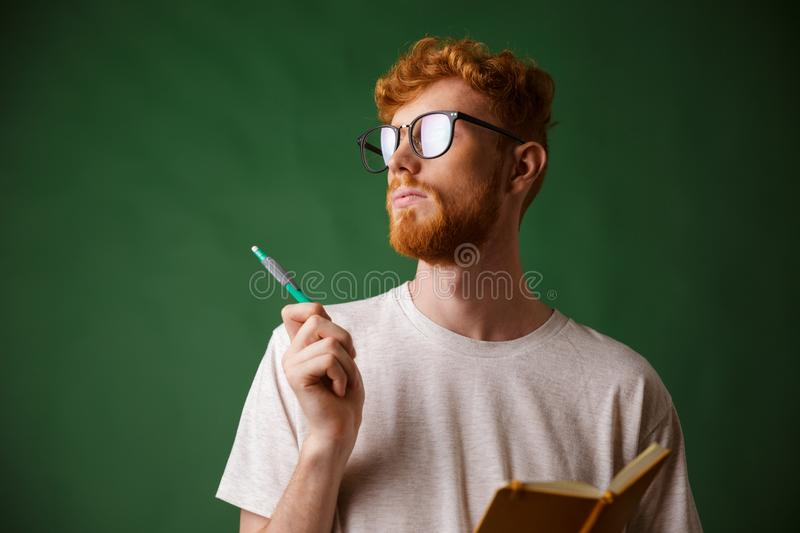 Close-up view of thinking bearded young man in white tshirt hold stock images