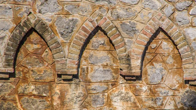 Bricks ornaments integrated into the wall. Close up view of three bricks ornaments integrated into the orange stone wall.Use for background. Opatija Croatia stock image