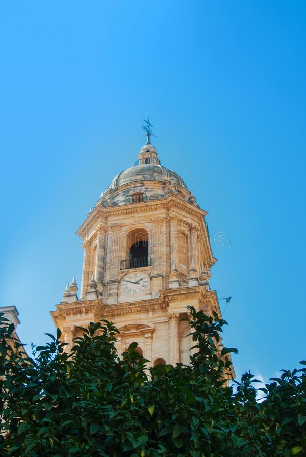 A close-up view to a bell tower of Malaga Cathedral over the ora royalty free stock photography