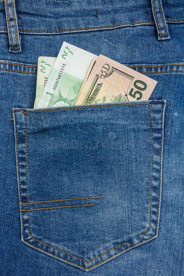 Close Up View to 100 euro and 50 dollar Banknotes Sticking Out From a Blue Jeans Pocket stock photography