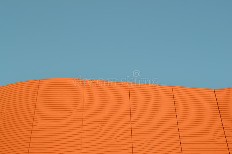 Close-up view to a modern asian architecture as a striped a large brown cement wall brightly illuminated. royalty free stock photo