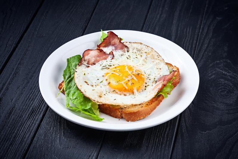 Close up view on toast with fried egg, bacon melted cheese and lettuce. Breakfast food. Fried toast on dark background. Snack. royalty free stock image