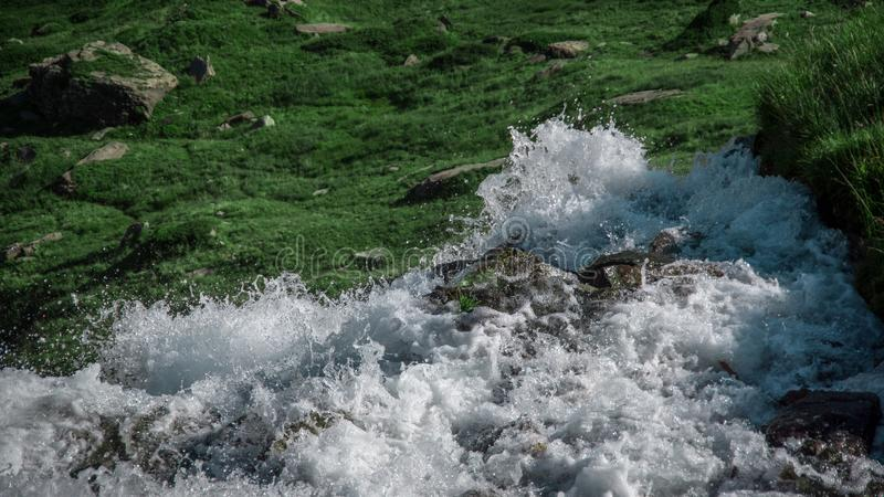 Waterfall falling down to the beautiful mountain green meadow. Close up view of the top of a waterfall falling down to the beautiful mountain green meadow royalty free stock photo