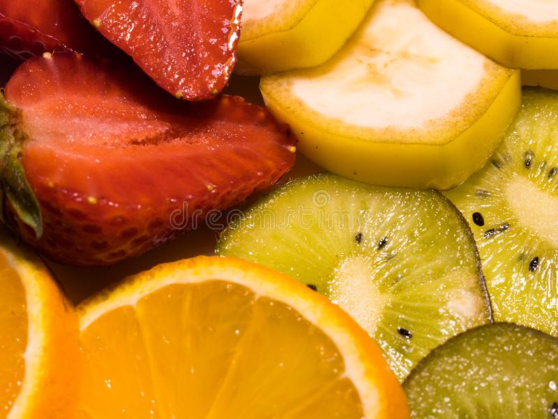 Close-up view on tropical fruits: banana, kiwi, orange, and strawberries royalty free stock images