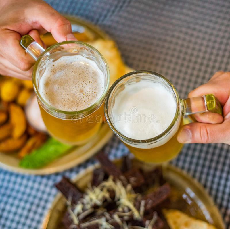 Two glass of beer in hand. Beer glasses clinking in bar or pub on table with food background. Close-up view of a two glass of beer in hand. Beer glasses clinking royalty free stock photo