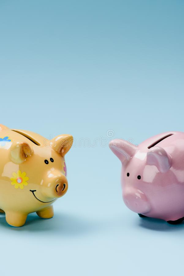 close up view of two yellow and pink piggy banks stock images