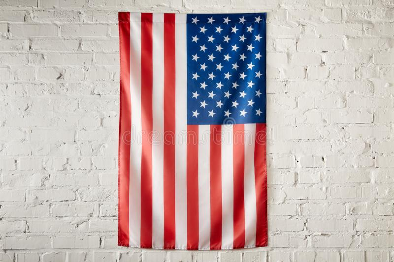 Close up view of united states of america flag on white brick wall stock image