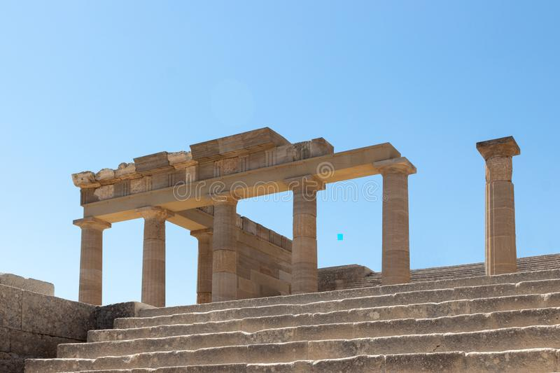 Ruins of stairs and the Hellenistic Stoa at the Acropolis of Lindos. Close-up view upstairs to the ruins of the Hellenistic Stoa with six columns remaining royalty free stock photography