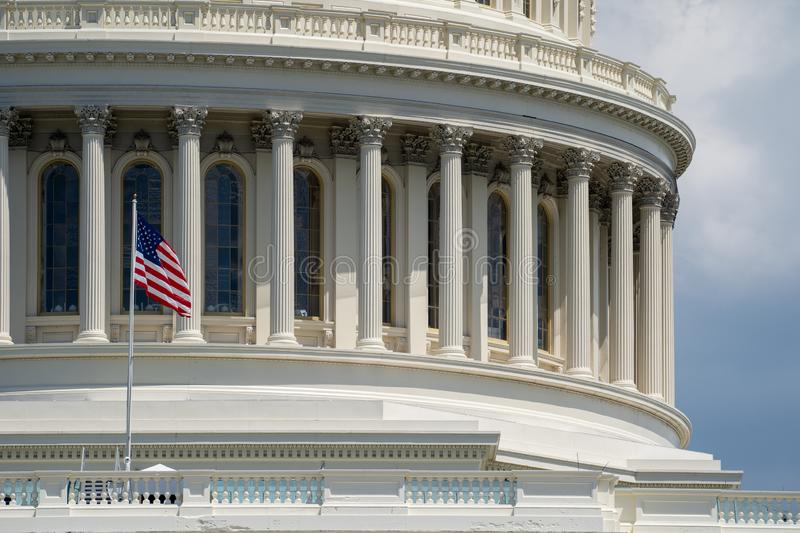 Close up view of the US Capitol Building dome and columns, with the American Flag.  royalty free stock images