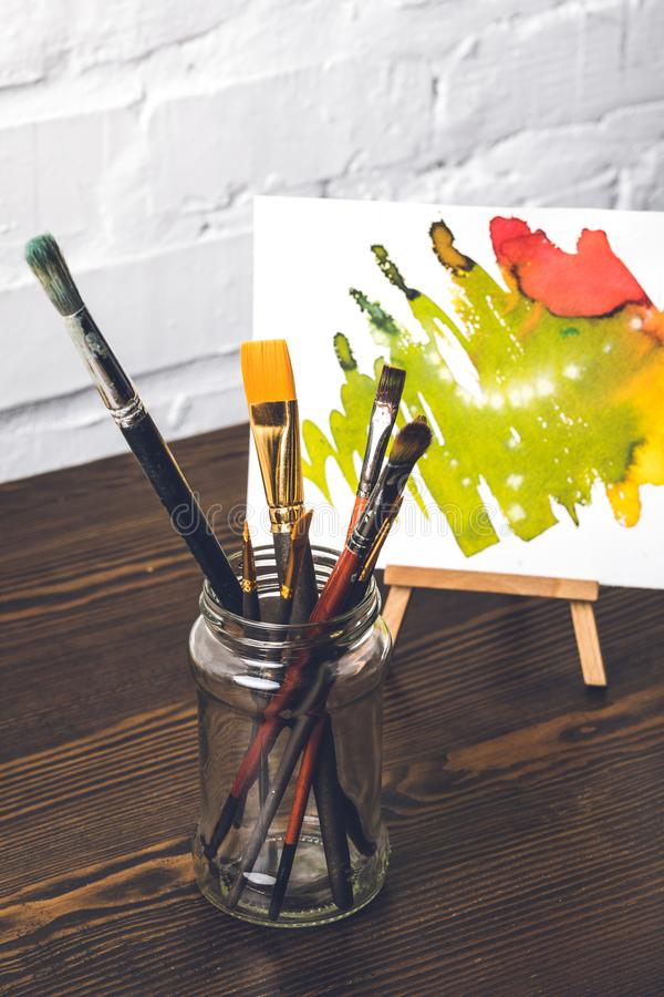 Various paint brushes in glass and abstract painting behind at designer workplace royalty free stock images