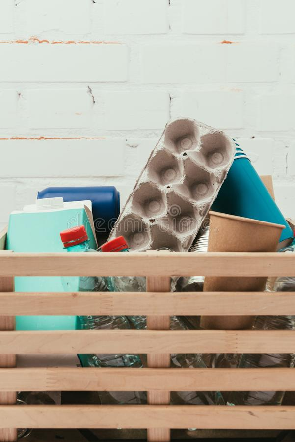 Close up view of various types of trash in wooden box with white brick wall. On background royalty free stock photography