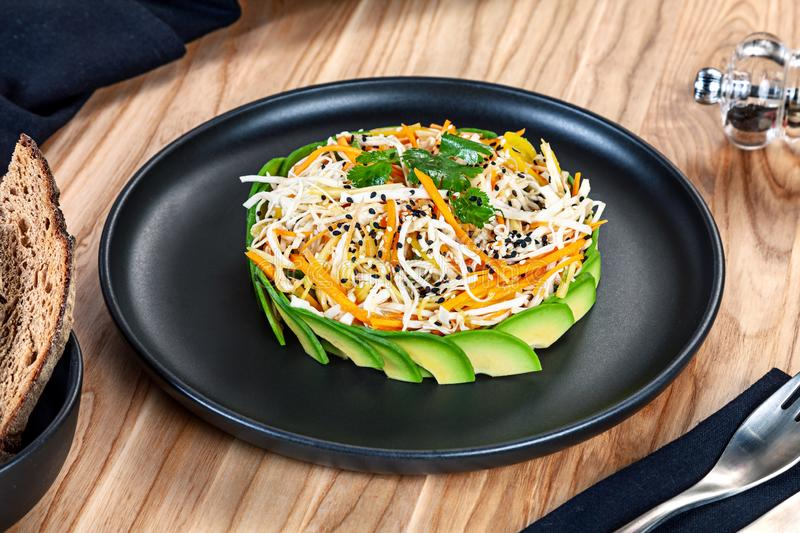 Close up view on vegan salad served on black plate on wooden background. RAW salad with carrot, cabbage, avocado. Healthy food royalty free stock images