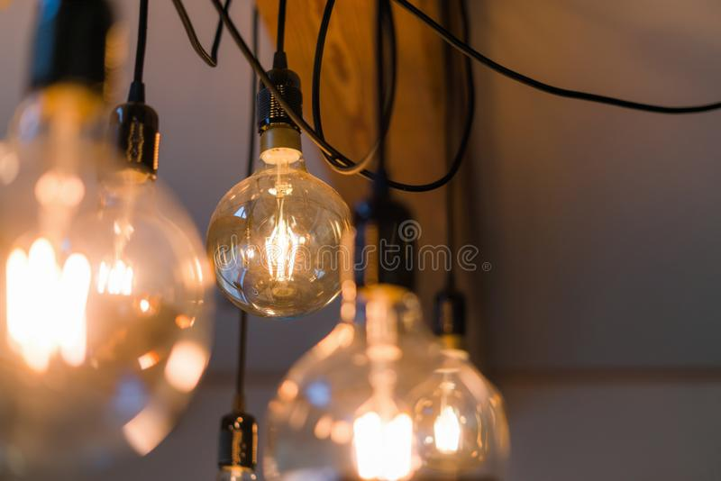 Close up view of vintage decorative light lamp bulb glowing on the ceiling indoors. Transparent lamps glowing with warm light stock photo