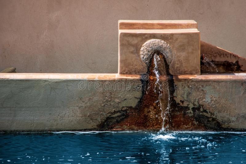 Close up view of a water fountain. Water coming from a hole on the wall covered with algae. Marrakesh, Morocco stock image