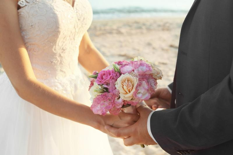 Close up view of wedding couple holding bouquet royalty free stock image
