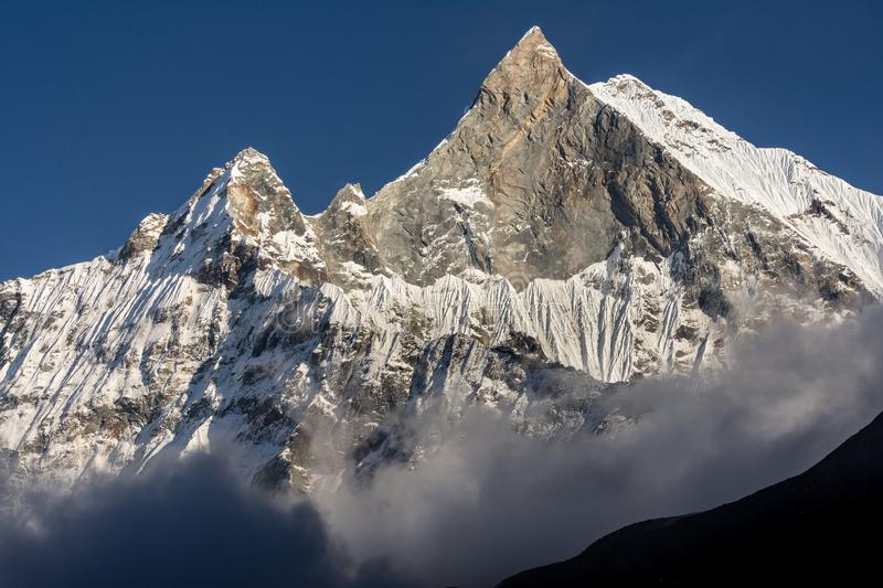 Close-up view of west face of Machapuchare peak Fish Tail emerging from the clouds in Nepal stock image