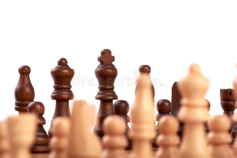 Close-up view of white and black chess pieces on a wooden chessboard in game. Isolated on white background. Close-up view of white and black chess pieces on a royalty free stock photos