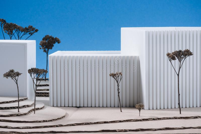 Close up view of white building model with miniature trees. On blue background stock photos