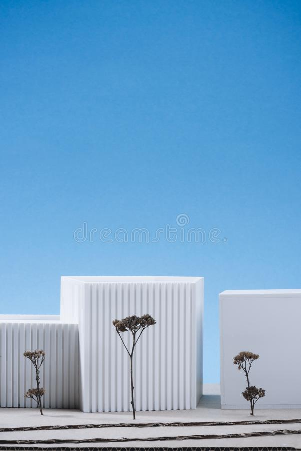 Close up view of white building model with miniature trees. On blue background stock image
