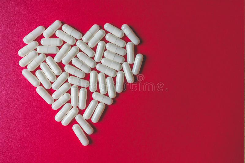Close up view of white capsules forming a heart on red background with space. Close up view of white capsules forming a heart shape on red background with copy royalty free stock photography