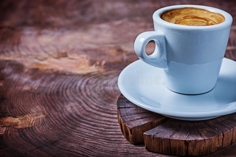 Close up view white coffee cup with capuchino on vintage wood cross cutted tree trunk stock image