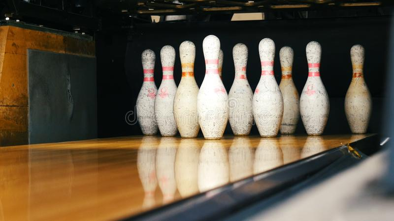 Close-up view of white pins standing in th end of bowling alley lane and rolling bowling ball in a sport club. Media. Close-up view of white pins standing in th royalty free stock photos