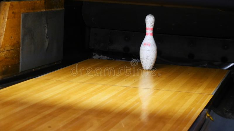Close-up view of white pins standing in th end of bowling alley lane and rolling bowling ball in a sport club. Media. Close-up view of white pins standing in th stock images