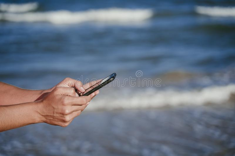 Close up view of woman hands holding mobile phone at the beach. Summer and technology concept stock photos