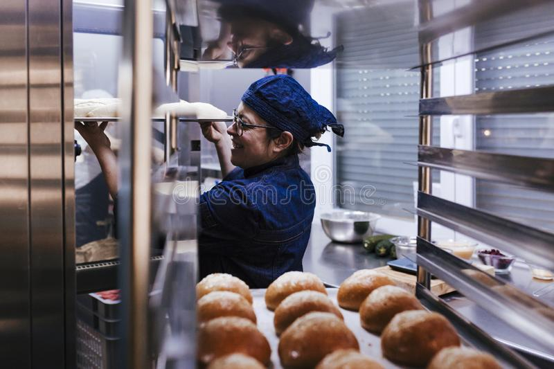 Close up view of woman holding holding rack of rolls in a bakery stock photography