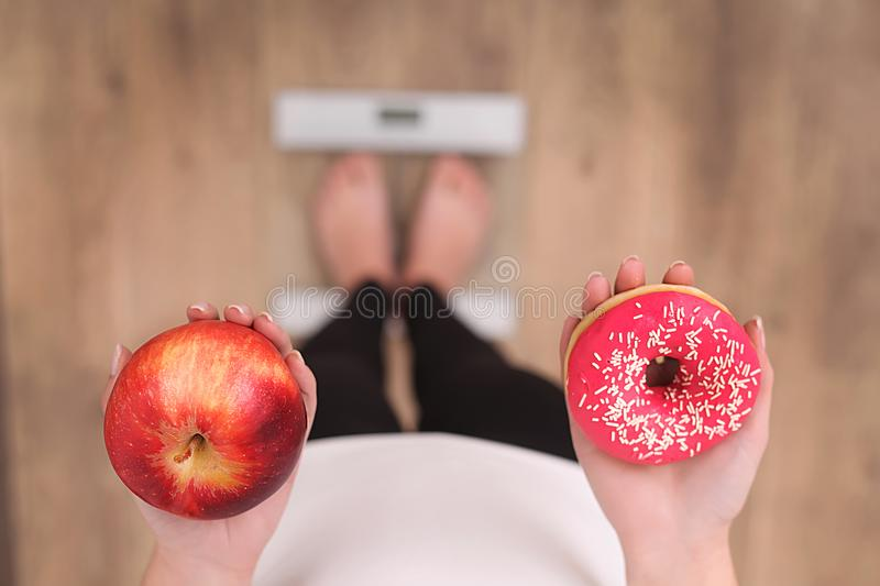 Close up view of woman making choice between apple and donut with blurred scales on background. Dieting concept.  royalty free stock image