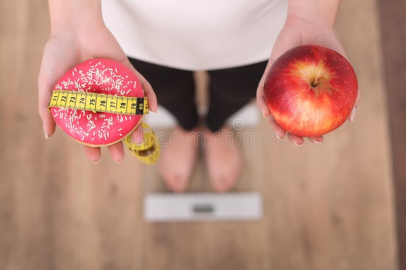 Close up view of woman making choice between apple and donut with blurred scales on background. Dieting concept.  royalty free stock images